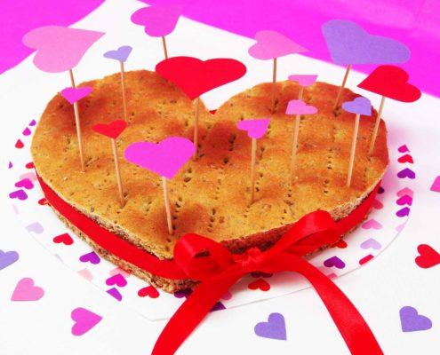 Brot in Herzform schön dekoriert mit einer roten Schleife